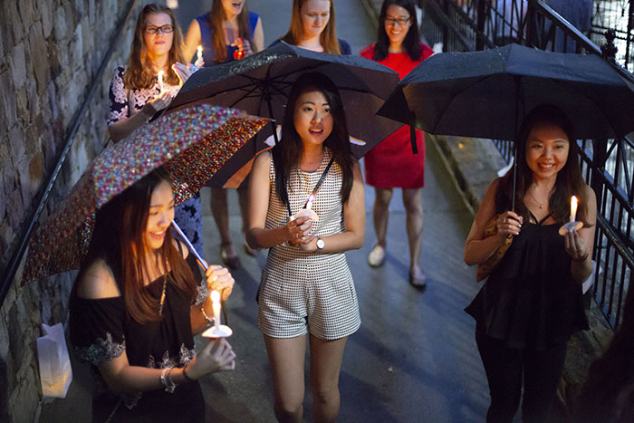 A group of students walk across the bridge with umbrellas