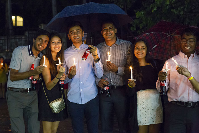 A group of students pose under shared umbrellas with their candles and Cokes