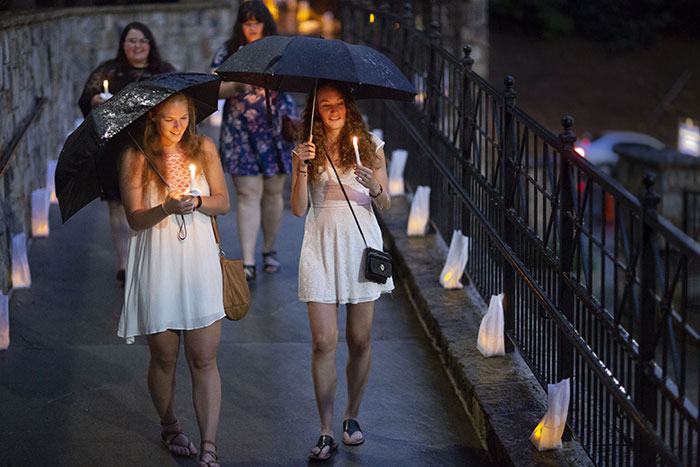Two young women carrying umbrellas and wearing white dresses hold candles as they cross the bridge