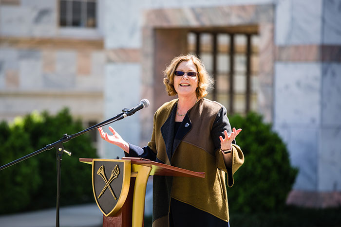 Emory President Claire E. Sterk speaks at a podium at the first Conversations on the Quad