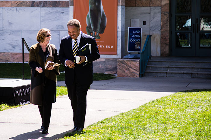 Robert M. Franklin and Emory President Claire E. Sterk laugh and chat as they walk at Conversations on the Quad