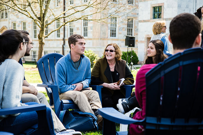 Emory President Claire E. Sterk kneels between two students, smiling as she speaks to them at Conversations on the Quad