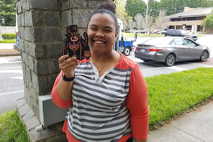 "A student poses with a wooden, black and orange ""Dooley Cat"" she found on Emory's campus"