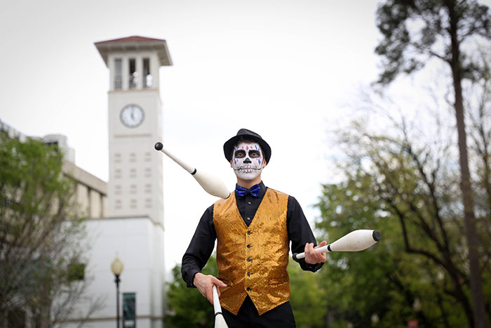 A performer with a painted skeleton face mask juggles three pins