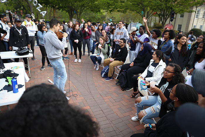 A student speaks to a large crowd at Dooley's Week