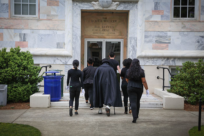 Dooley walks through campus with groupies all dressed in black clothing and sunglasses