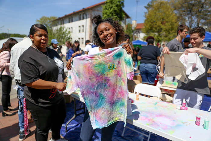 An Emory student holds up her tie-died t-shirts for Dooley's Week