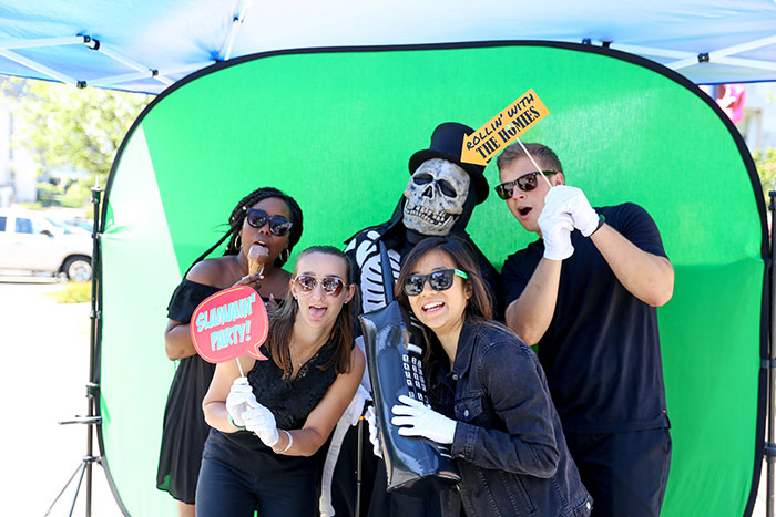 Four Emory students and Dooley pose with props in front of a green screen in a photobooth for Dooley's Week