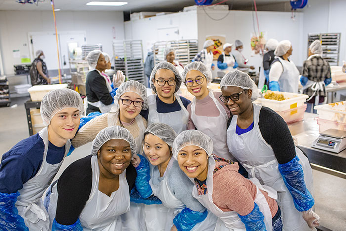 A group of students wear hair nets and aprons as they prepare meals at Project Open Hand