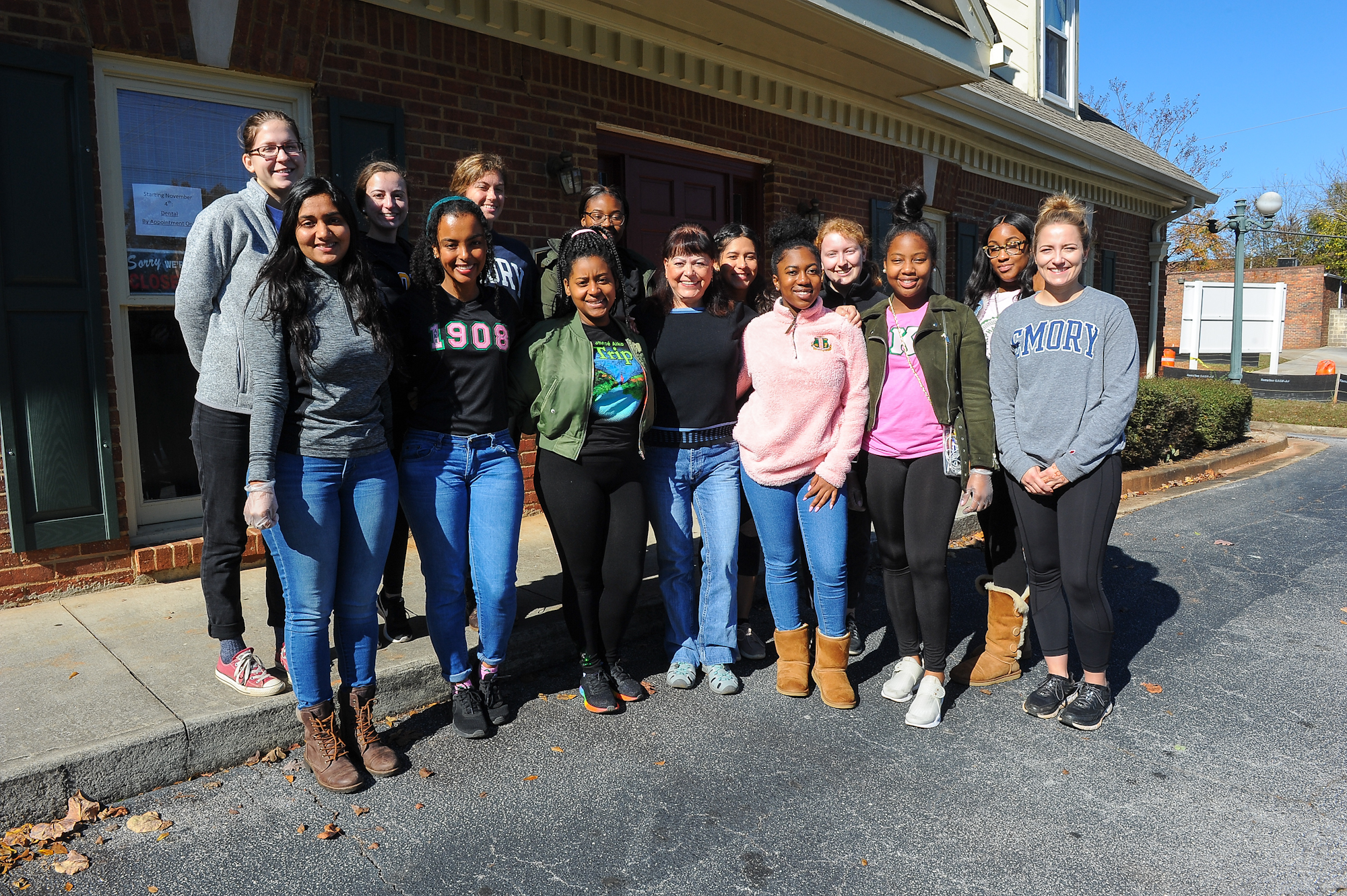 A group of student volunteers pose outside the clinic at Harriet Tubman Women's Clinic