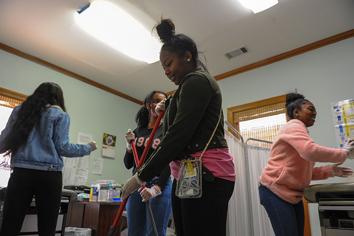 Students use brooms and mops as they help clean at Harriet Tubman Women's Clinic