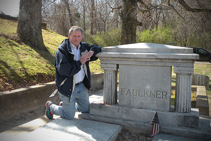 Clyde Partin Jr., a physician and professor in the Emory School of Medicine, poses at Faulkner¿s grave.