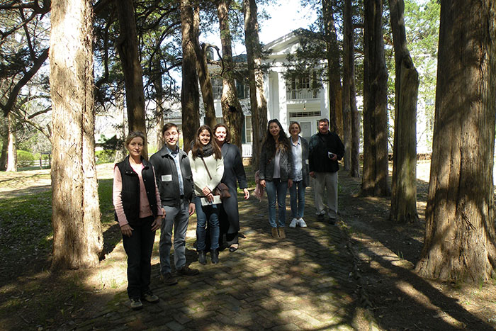 A group of Emory students stand in front of Rowan Oak