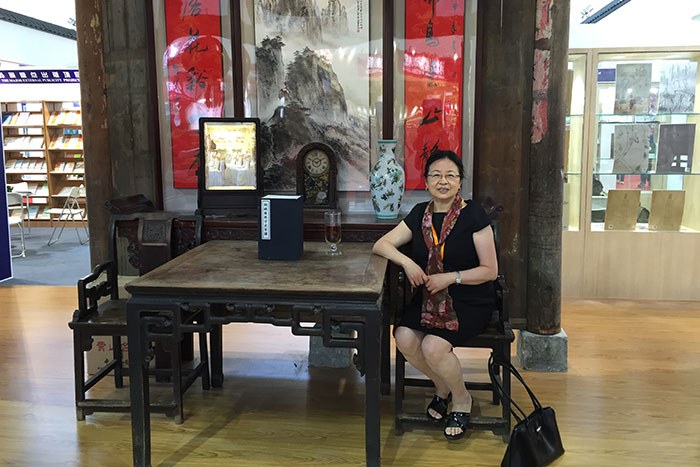 Chinese Studies librarian Guo-hua Wang sits at the entrance to the booth of her native province of Anhui, which is decorated like the living room of a home, at the Beijing International Book Fair last year.