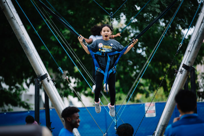 A little girl is suspended by bungee cords as she jumps on a trampoline at the Homecoming Festival