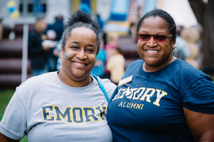 Two women wearing Emory t-shirts pose at the end of the Homecoming concert