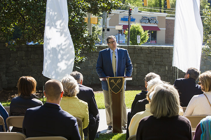 David Payne stands at a podium and addresses a small crowd at the PATH at Emory opening.