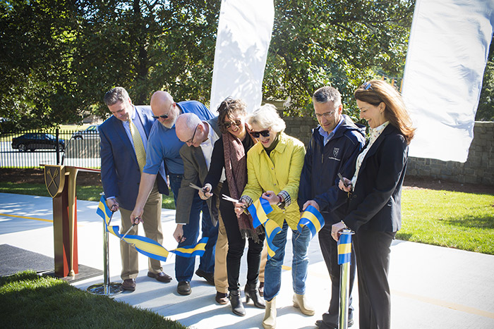 Seven representatives of Emory, the PATH Foundation and the City of Atlanta cut a large blue and yellow ribbon to officially open the new path.