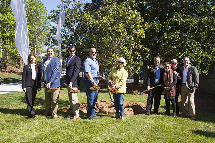 The same seven representatives pose with shovels as they plant a magnolia tree.