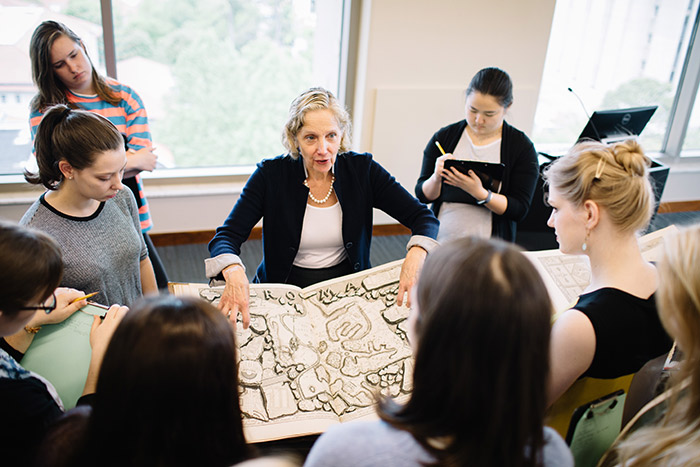 Art history professor Sarah McPhee and graduate student and Mellon Fellow Abbey Hafer point to details on an etching while speaking to a class.
