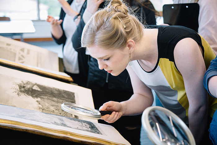 A student uses a magnifying glass to examine the details on a Piranesi etching.