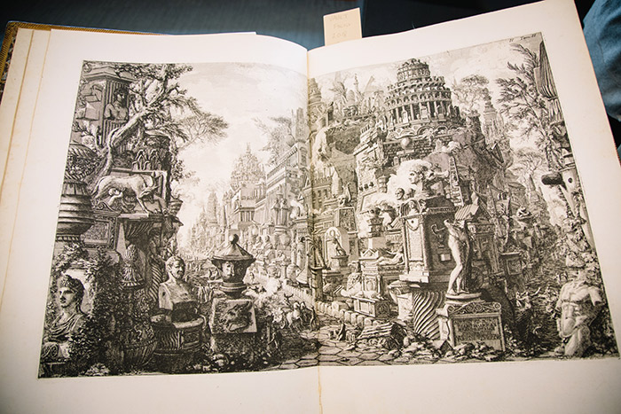 A close-up of a Piranesi etching, showcasing a black and white sketch in a book showcasing ancient Roman statues and buildings