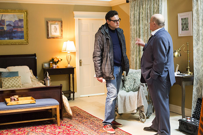 "Rob Barracano and Michael Ironside speak to each other on set of ""Fran K."" They stand in a bedroom set, full of bedroom furniture and props."