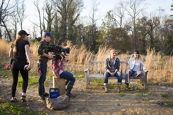 Emory students work with a professional film crew to film an outside scene on a bench near Emory's campus.