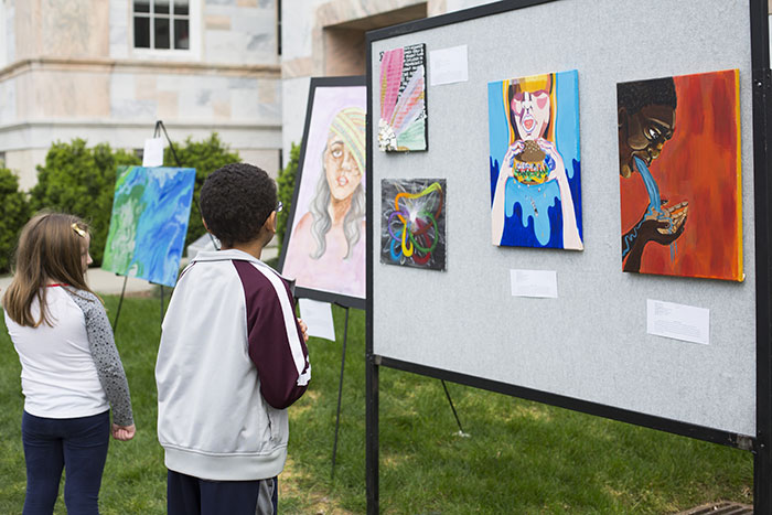 Two young visitors view artwork on display on the Quad.