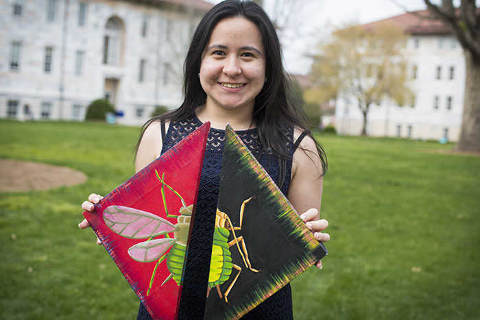 Pamela Romero holds her artwork up for the camera. The DNA painted along the edges of the canvases is the same, except that different genes are switched on, showing how aphids can develop wings in response to environmental change.
