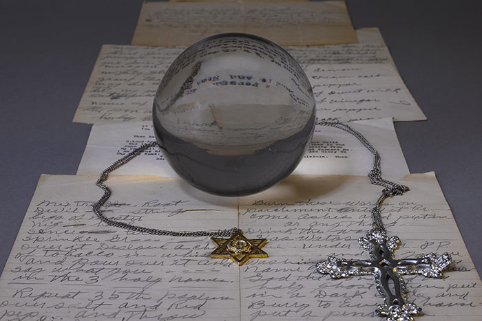 A crystal ball and a handwritten page of spells from the papers of Mamie Wade Avant