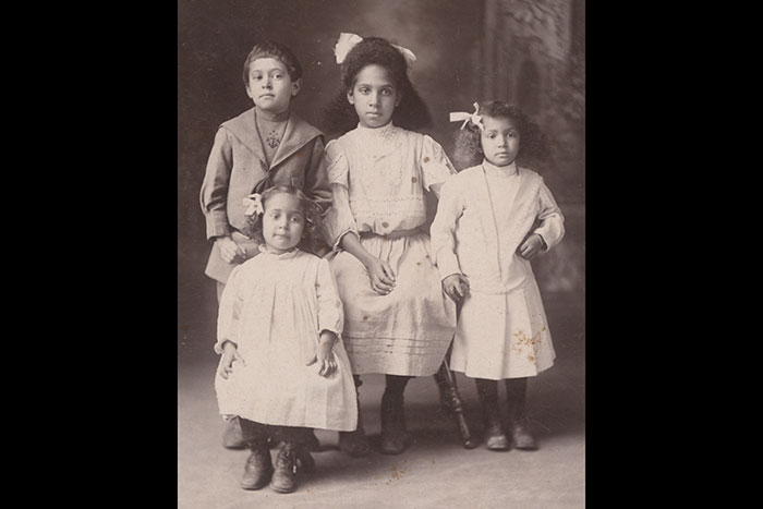 Three girls and one boy pose for a photo