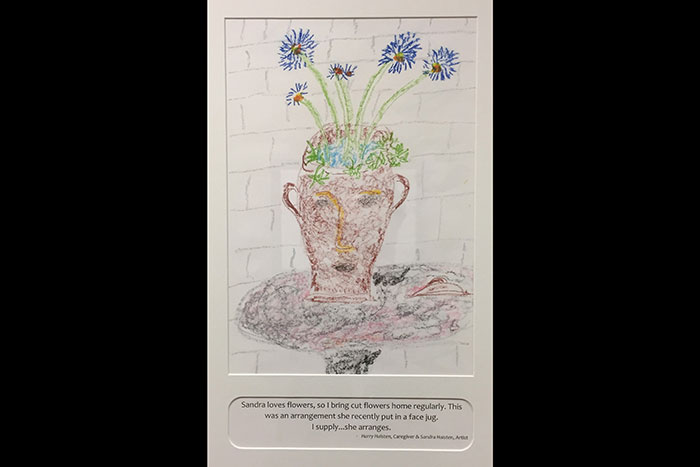 "A drawing of flowers in a jug by Sandra Haisten. The caption on the image reads: ""Sandra loves flowers, so I bring cut flowers home regularly. This was an arrangement she recently put in a face jug. I supply...she arranges. - Harry Haisten, Caregiver and Sandra Haisten, Artist"""