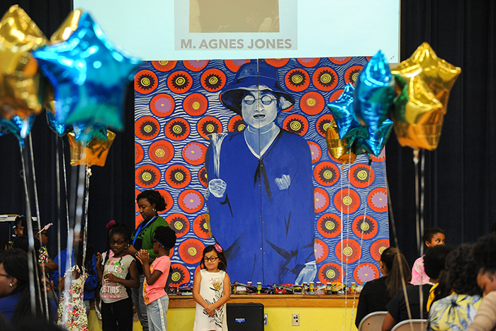 Students stand in front of a colorful mural of Mary Agnes Boswell Jones
