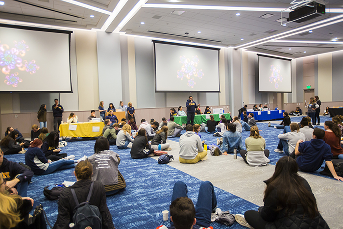 Students sit on a floor of the student center