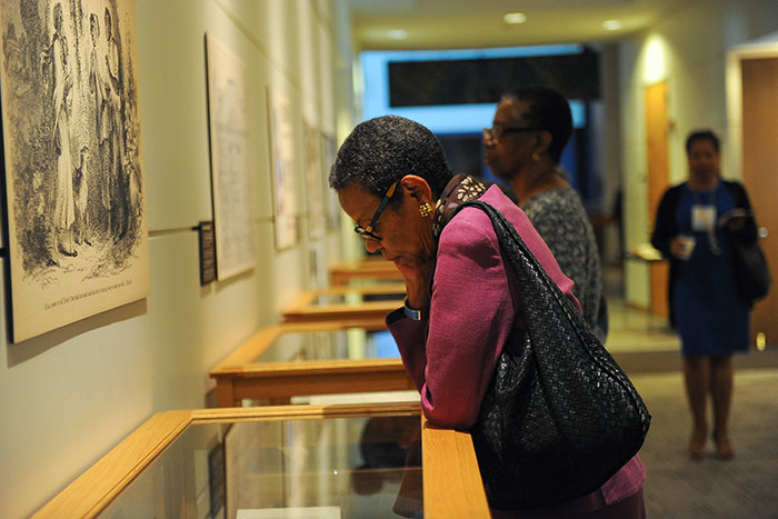 "A woman looks at an item on display at the ""Framing Shadows"" exhibit"
