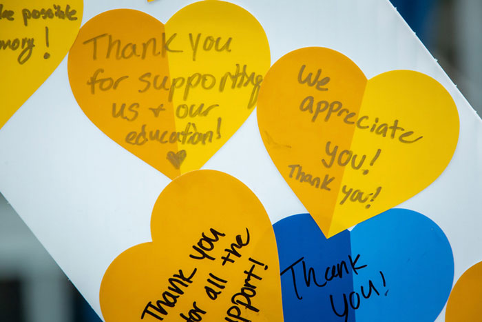 A close-up of thank you notes written on gold and blue hearts