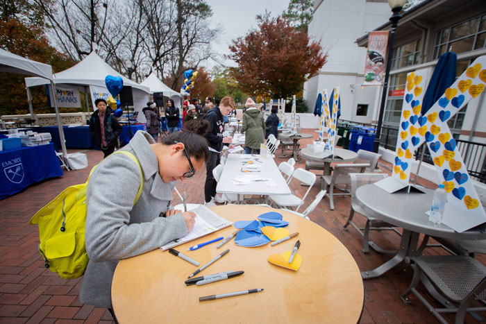 Students outside of Cox Hall write thank you notes to donors