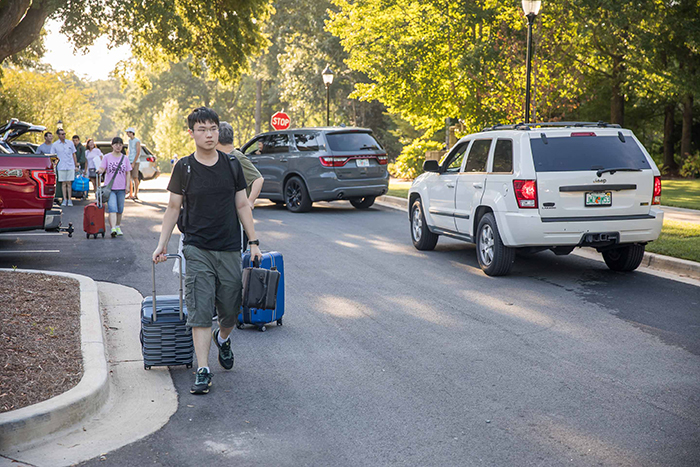 A student pulls suitcases on Move-In Day