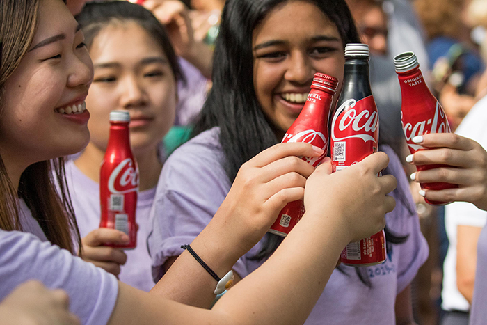 Students hold bottles of Coke high for the Coke Toast