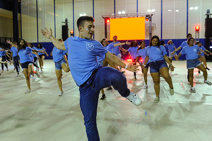 Students in blue t-shirts dance at Songfest