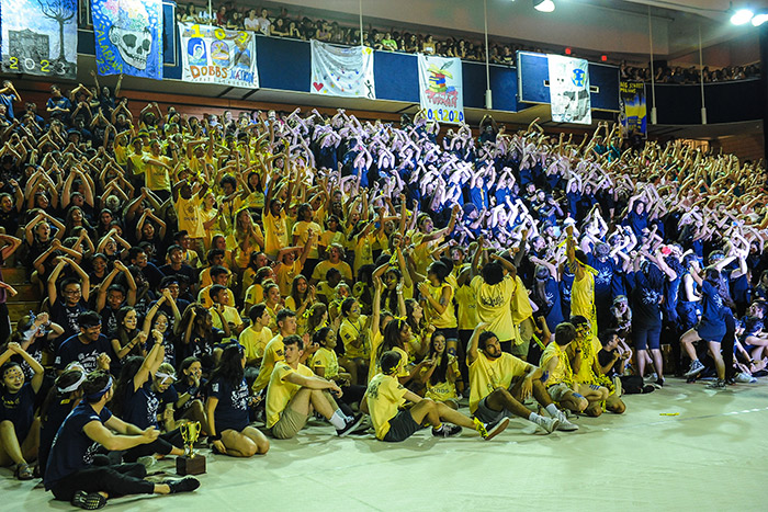 A large crowd of students in multi-colored t-shirts cheer at Songfest