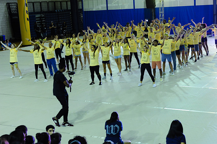 Students from Dobbs hall wear yellow t-shirts and sing together