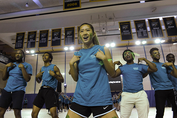 Students in blue t-shirts dance and sing