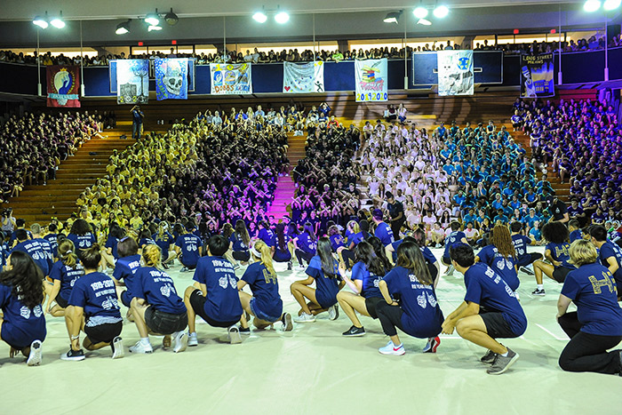 Students in blue t-shirts squat in sync at Songfest
