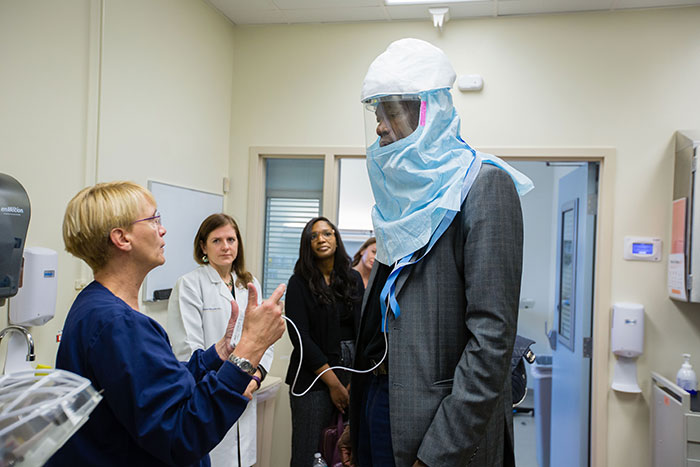 Dikembe Mutombo tries on a powered air-purifying respirator, which looks like a large blue hood with a clear plastic mask to look out through