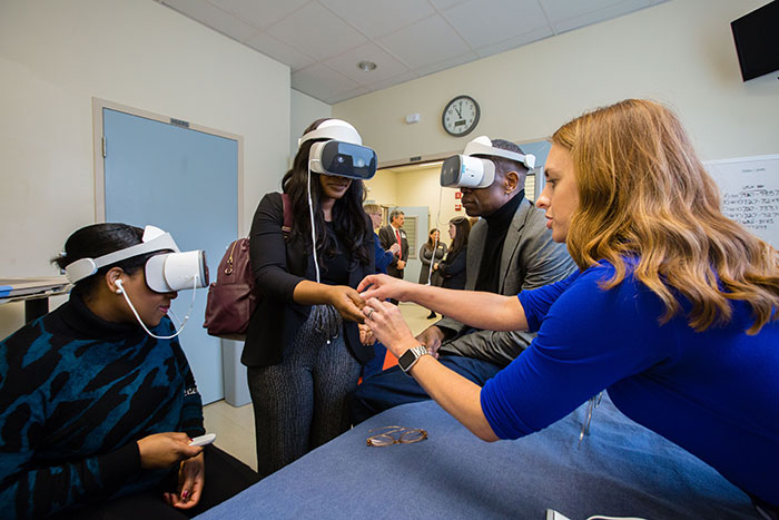 Dikembe Mutombo and others wear virtual reality headsets to view how health care workers care for Ebola patients
