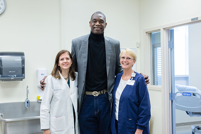 Dikembe Mutombo poses with Emory infectious disease physician Colleen Kraft (left) and critical care nurse Jill Morgan (right) during a visit to the Serious Communicable Diseases Unit.