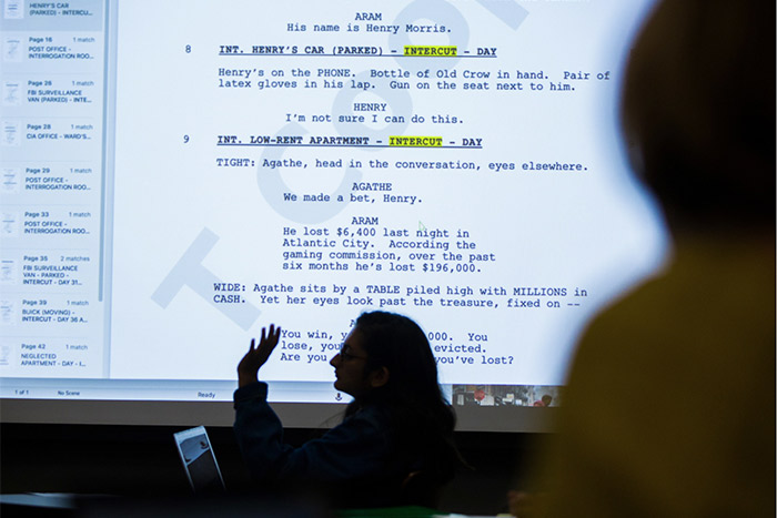 A student speaks, a script is projected on a screen behind them