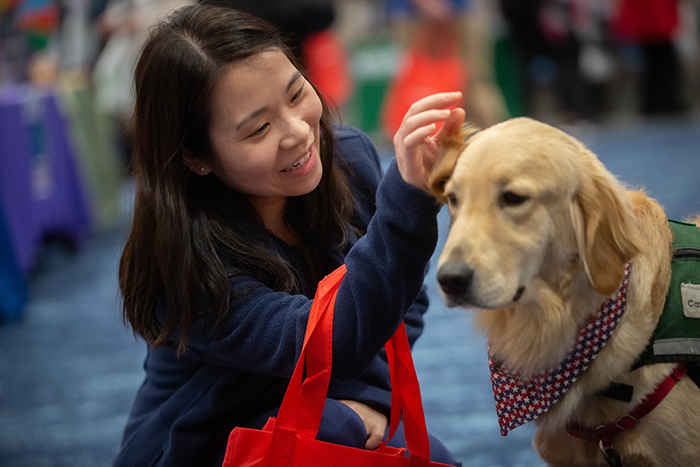 An Emory employee pets a therapy dog